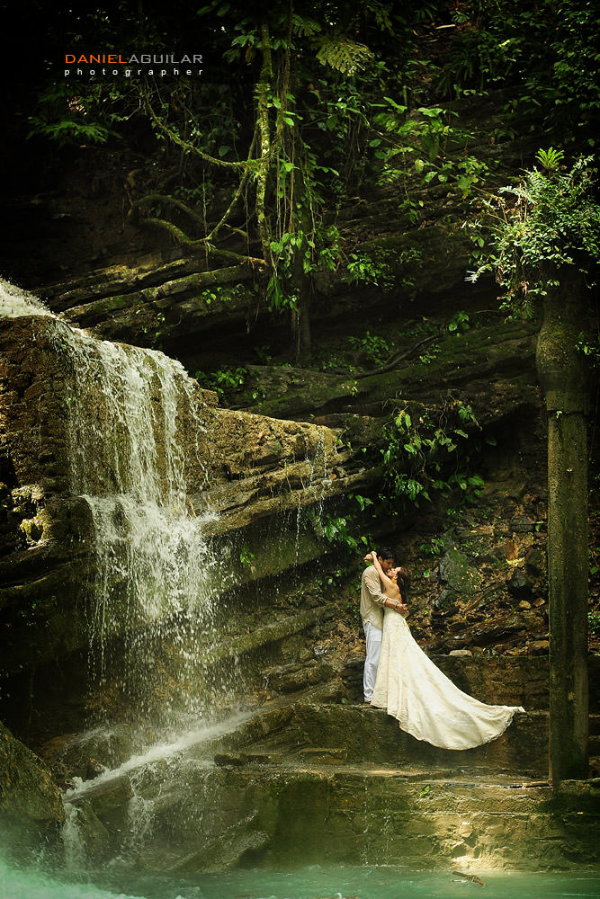 Bride and groom kissing under a cascade in Xilitla